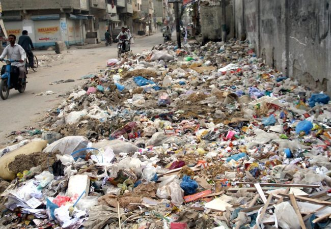 Pic14-054 KARACHI: Oct 14 – A view of garbage spreading on Azizabad's road creating problems for commuters. Garbage and sewage crisis are amongst the many tragedies that have afflicted Karachi over decades. In some areas situation is even worst, like sewage water enters homes, which gives rise to many harmful diseases. ONLINE PHOTO by Syed Asif Ali