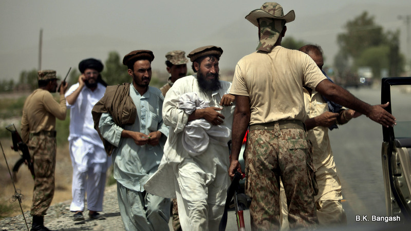 Pakistani army troops allow tribal people to travel to north Waziristan after a clearance at a check post outside Bannu, Pakistan, Wednesday, June 18, 2014. T
