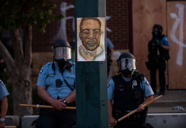 "MINNEAPOLIS, MN - MAY 27: A portrait of George Floyd hangs on a street light pole as police officers stand guard at the Third Police Precinct during a face off with a group of protesters on May 27, 2020 in Minneapolis, Minnesota.  The station has become the site of an ongoing protest after the police killing of George Floyd. Four Minneapolis police officers have been fired after a video taken by a bystander was posted on social media showing Floyd's neck being pinned to the ground by an officer as he repeatedly said, ""I can't breathe"". Floyd was later pronounced dead while in police custody after being transported to Hennepin County Medical Center.  (Photo by Stephen Maturen/Getty Images)"