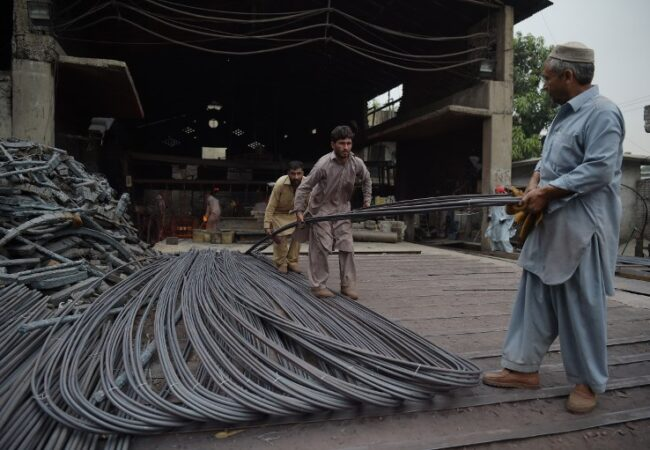 Pakistani men carry steel rods at a mill during International Labour Day in Islamabad on May 1, 2018. (Photo by AAMIR QURESHI / AFP)